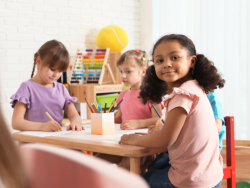 Adorable children drawing together at table indoors. Kindergarten playtime activities